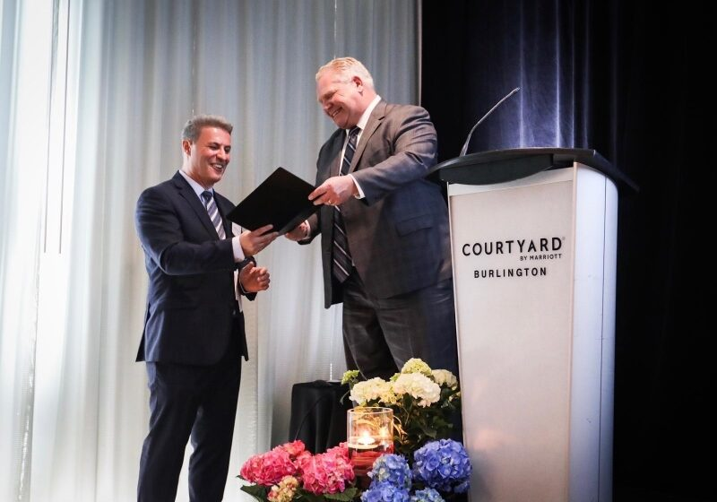 Premier Doug Ford presenting Official Grand Opening letter to Mr. Domenic Fuda, Hotel Partner and President of TriAxis Group of Companies